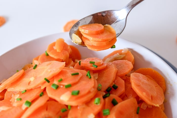 carrot salad in bowl with silver spoon lifting carrots away