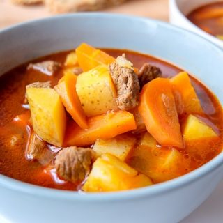 close up of bowl of goulash with potatoes and carrots