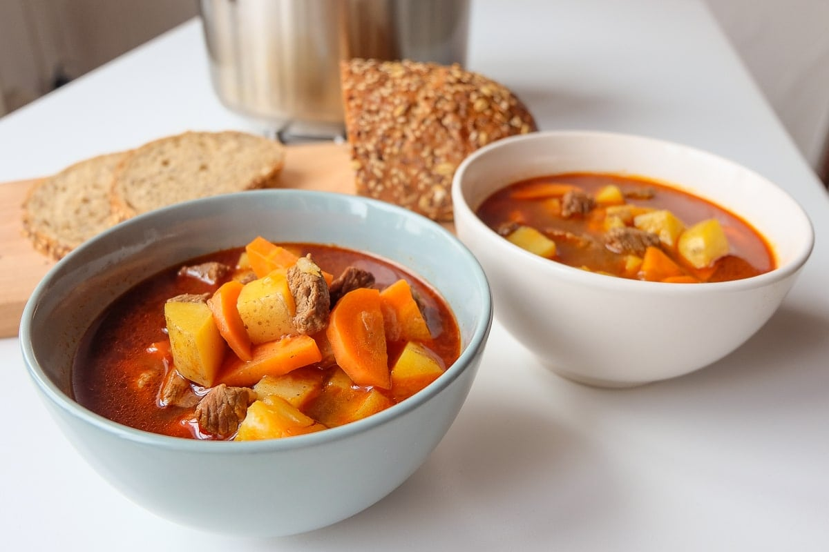 two bowls of hungarian goulash with bread and silver pot