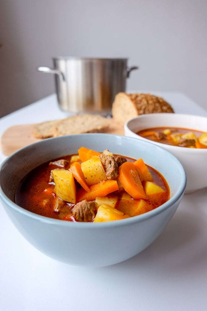 blue bowl of hungarian goulash soup on white table with bread and silver pot behind