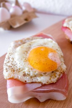 fried egg on ham and bread on wooden cutting board strammer max recipe