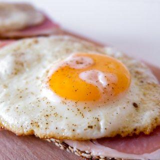 large fried egg yolk on ham and cutting board