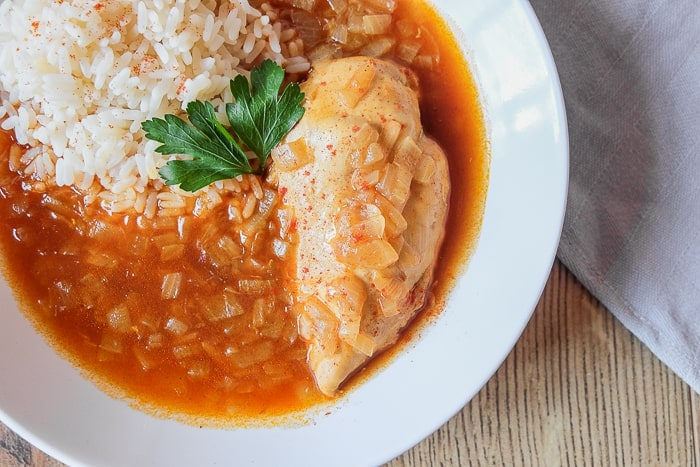 close up shot of chicken breast in a bowl with red paprikash sauce and rice