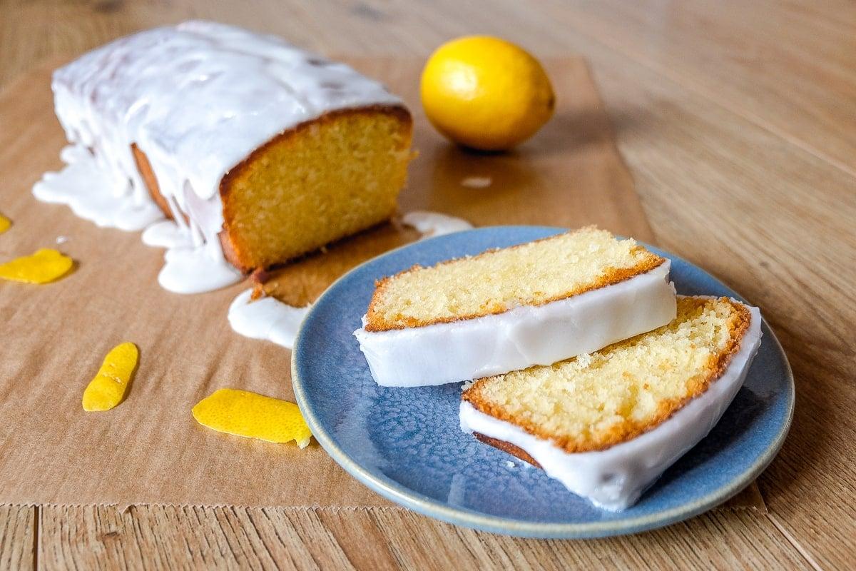 slices of easy lemon cake on blue plate with full cake behind