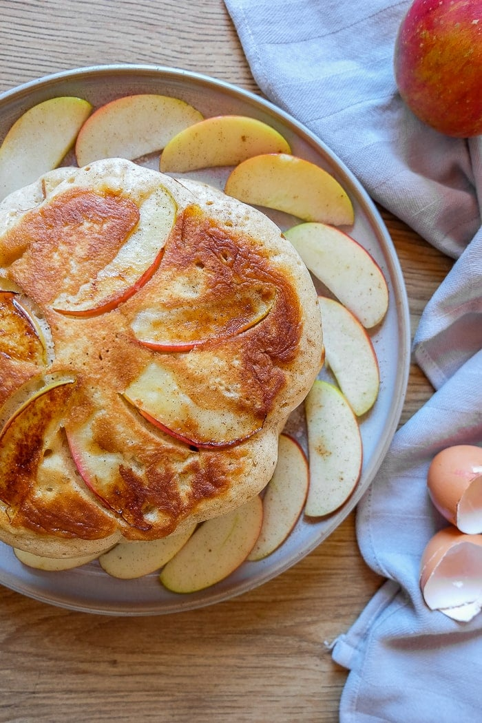 round german apple pancakes on plate with apple slices and napkin around