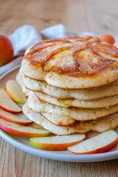 stack of german apple pancakes on plate with apple slices around