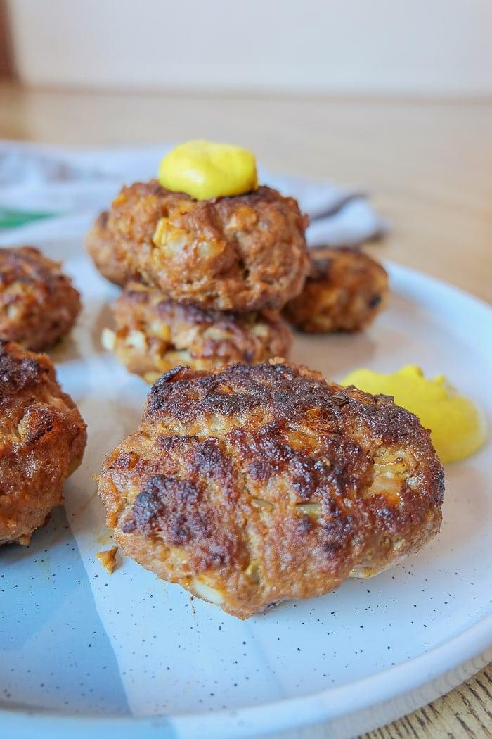 german meatballs on blue platter with mustard beside