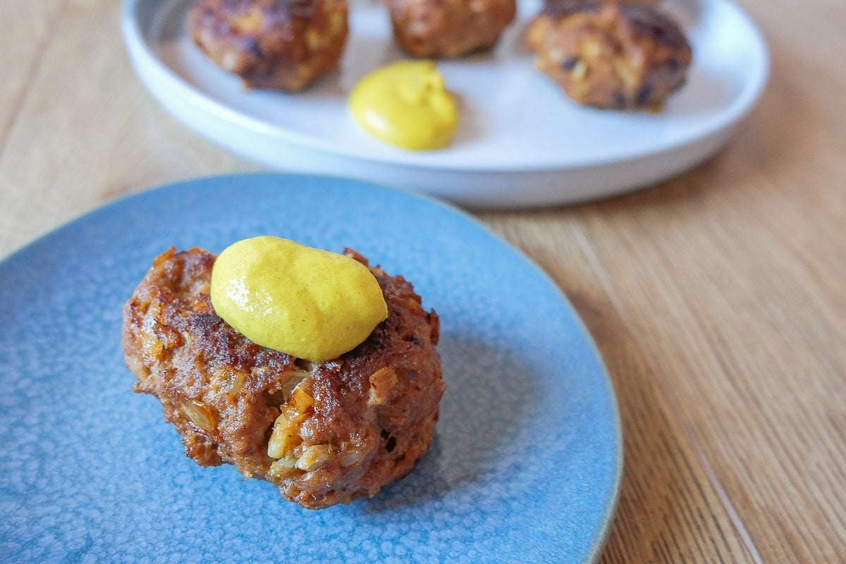 single german meatball with mustard on top on blue plate