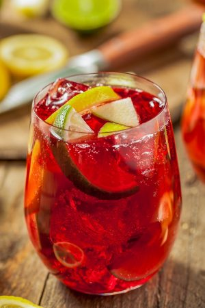 glass full of red sangria recipes with fruit and ice cubes