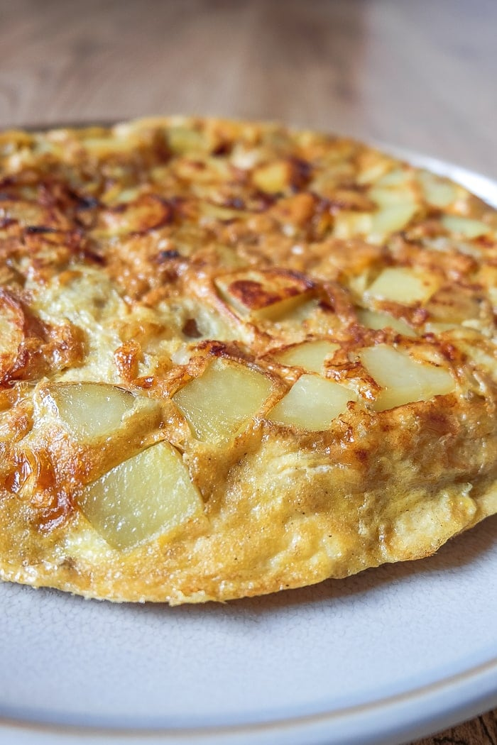 round yellow spanish tortilla omelette on grey plate