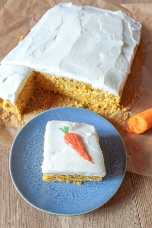 slice of easy carrot cake with carrot-shaped icing on blue plate