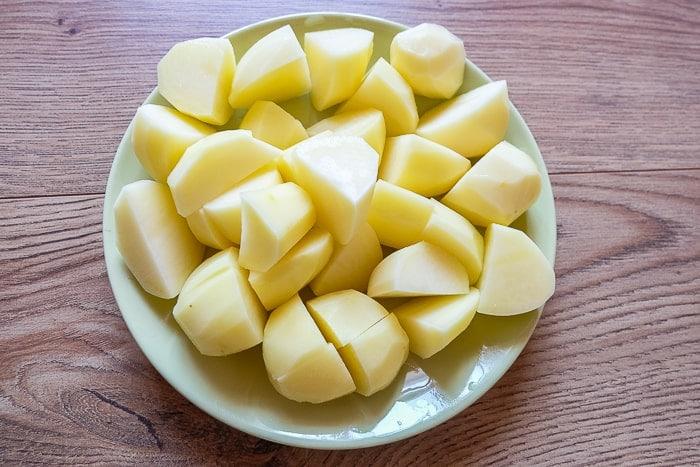 cut up peeled potatoes on a plate