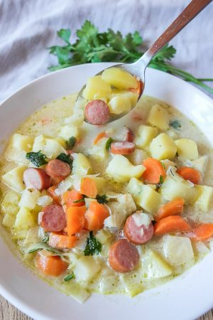 colourful vegetables in german potato soup with silver spoon in white bowl