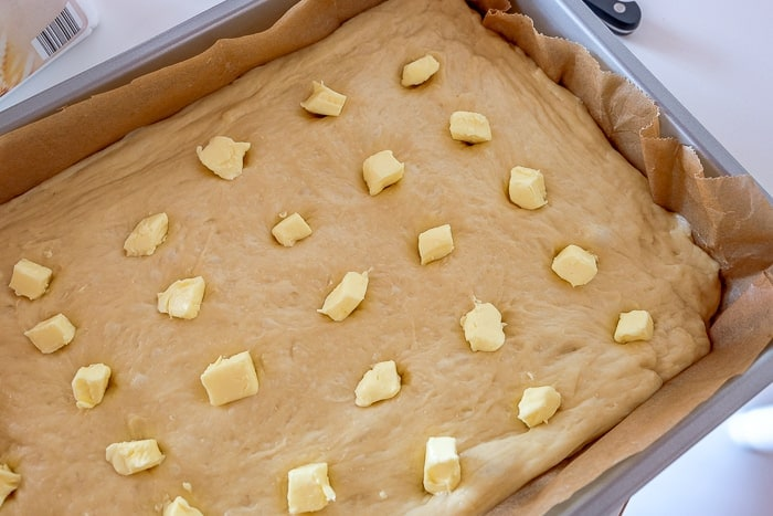 german butter cake dough in pan with butter chunks pressed on top