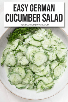 Slightly creamy cucumber salad in a bowl on white background with text overlay