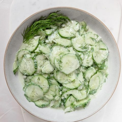 bowl of green german cucumber salad with dill on white marble