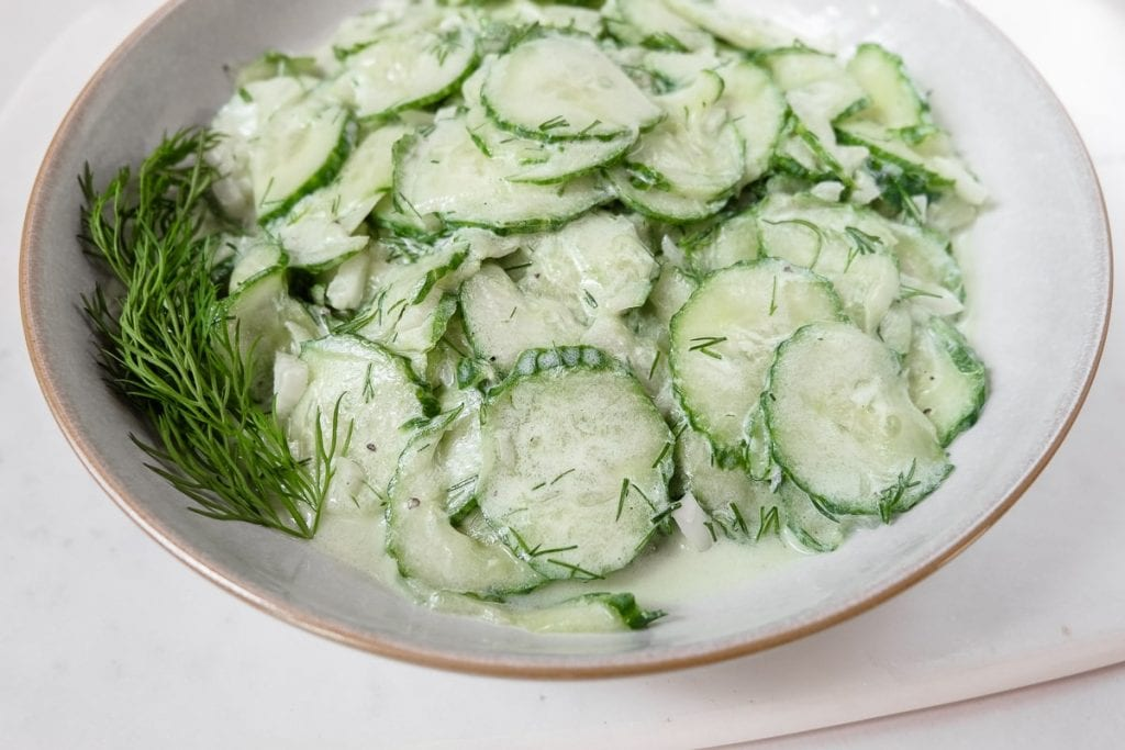 sliced cucumbers in white bowl on marble slab