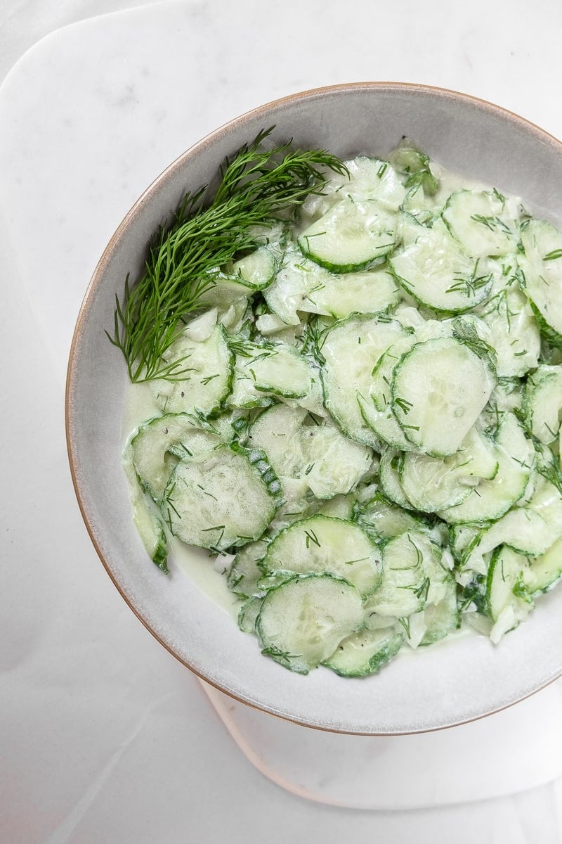 sliced cucumbers in german salad in bowl on white marble