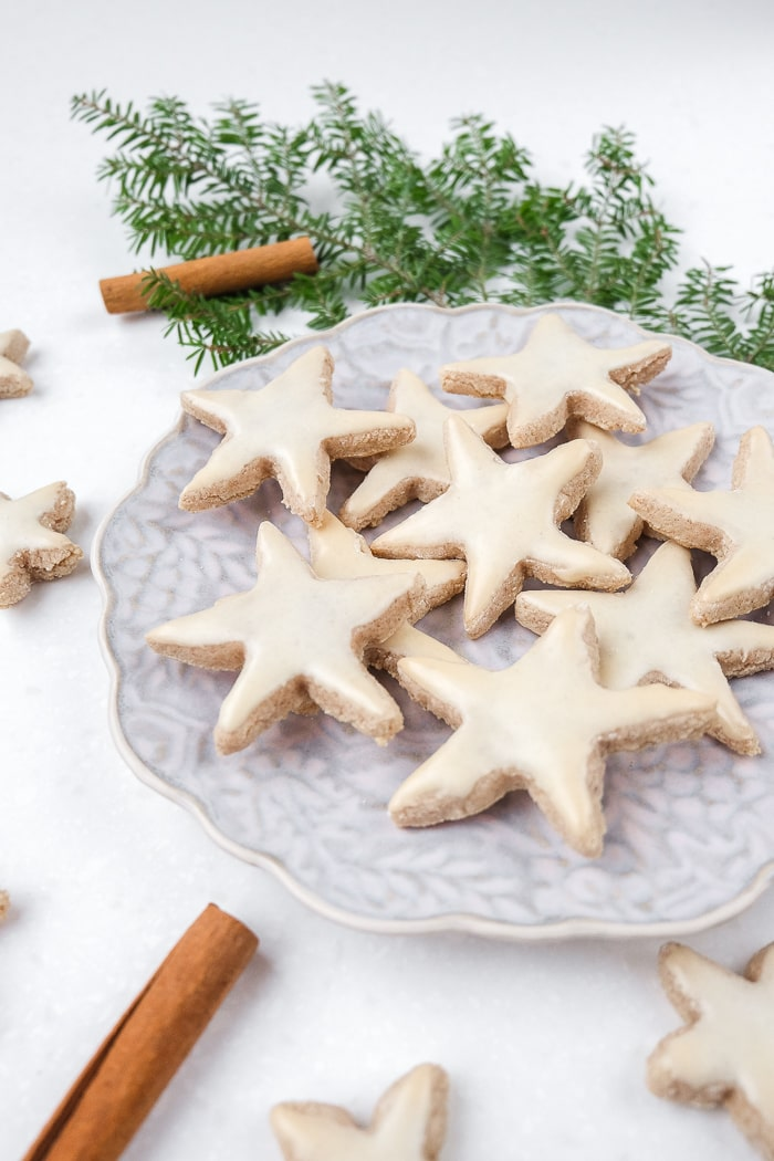 cinnamon star cookies on a plate with green branch behind