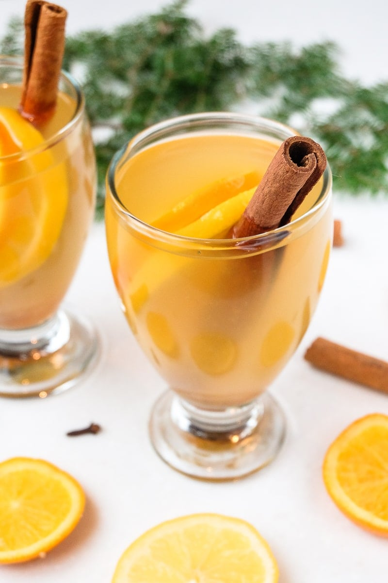 glass of german mulled white wine with oranges and cinnamon sticks around