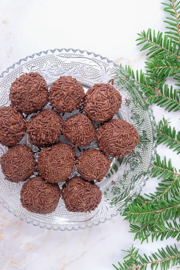 brown german rum balls on clear plate with green beside