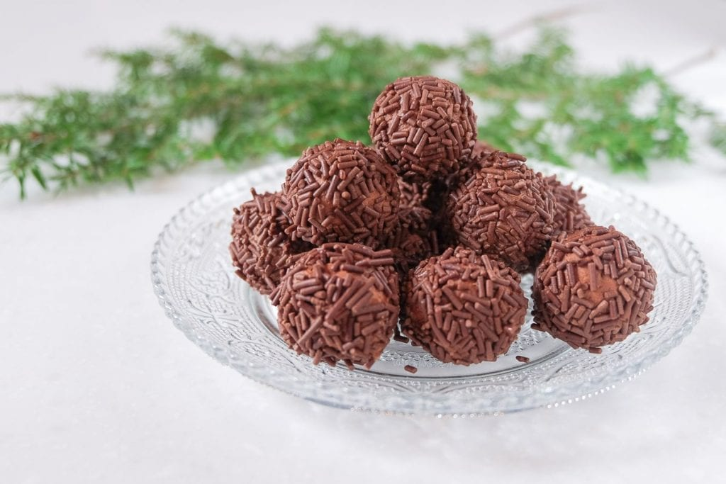 stack of german rum balls on clear plate with green branch behind
