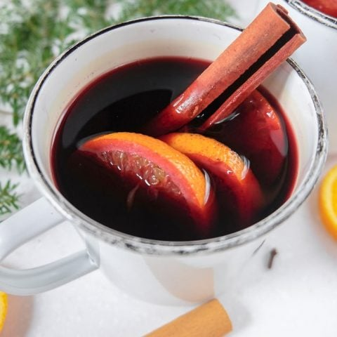 mug of red german mulled wine with cinnamon stick
