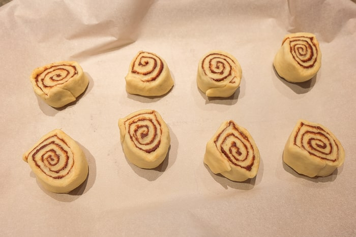 cut pieces of cinnamon roll dough on parchment paper
