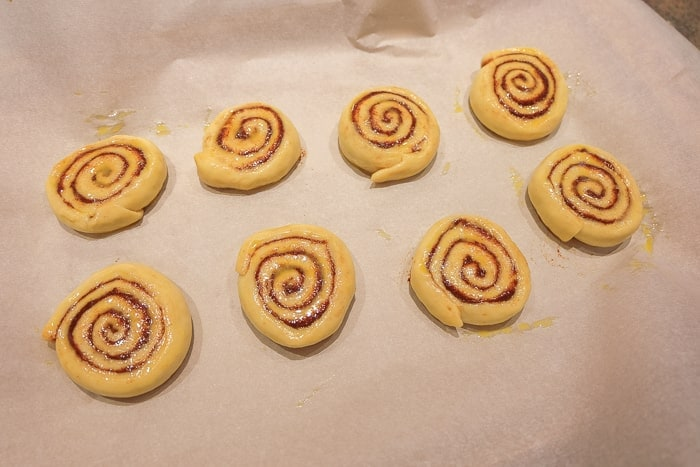 raw cinnamon rolls on parchment paper with egg wash
