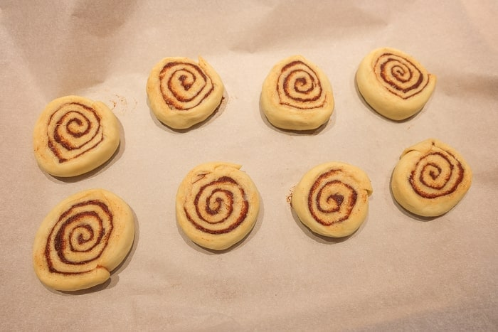 flattened cinnamon roll dough on white parchment paper