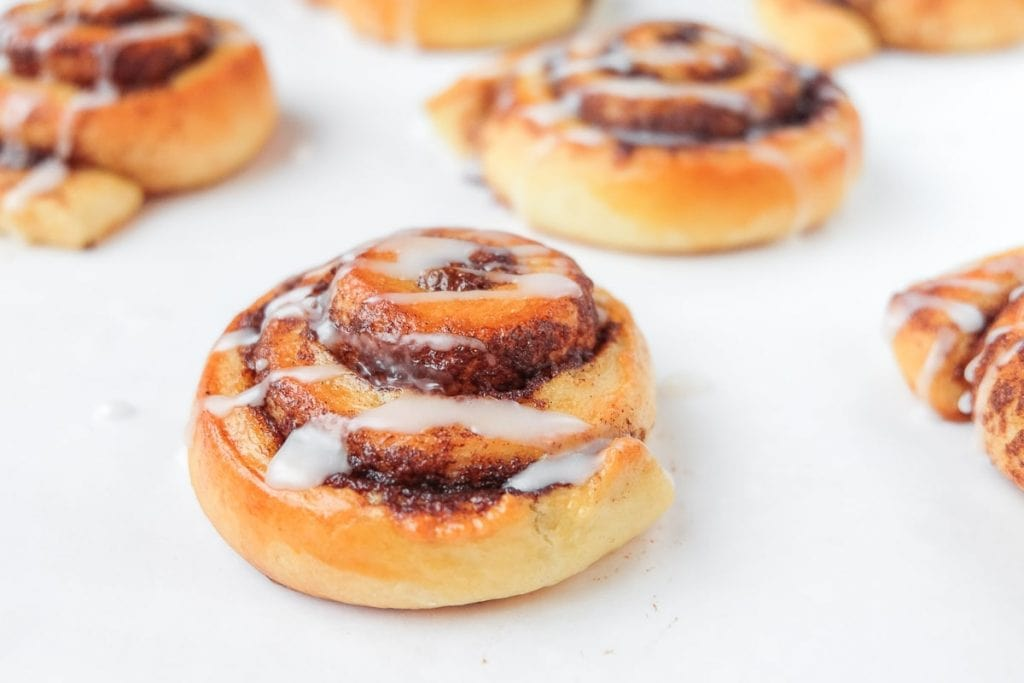 cinnamon buns with white icing on counter top