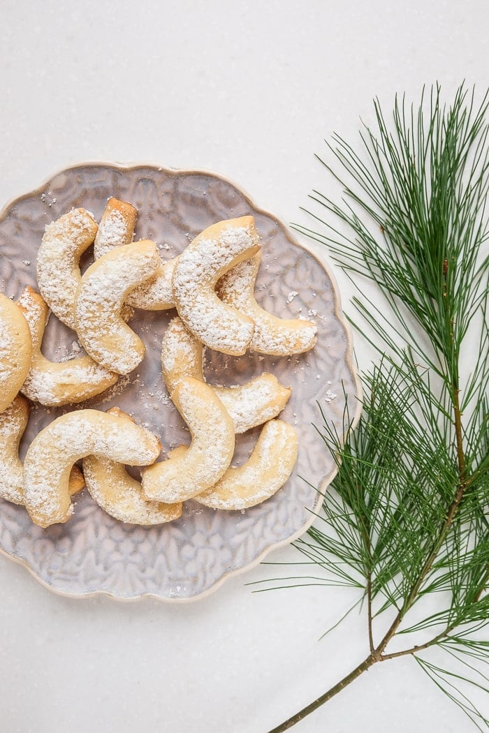 plate of vanilla cookies with pine tree branch beside