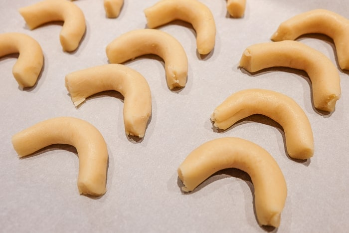 raw cookie dough in crescent shapes on baking sheet