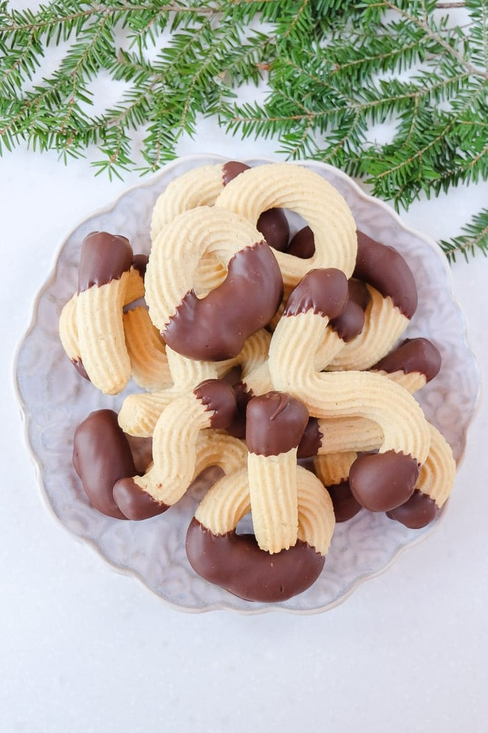 german spritz cookies on plate with green christmas branch