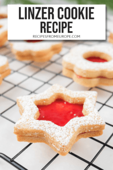 Photo of linzer cookie in star shape with red jam on cooling rack with text overlay for Pinterest