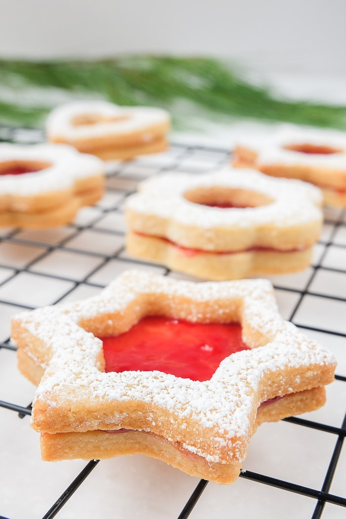 close up shot of star linzer cookie with red jam on cookie rack