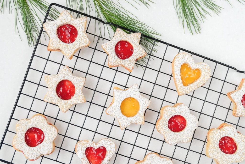 colorful linzer cookies on black cookie cooling tray