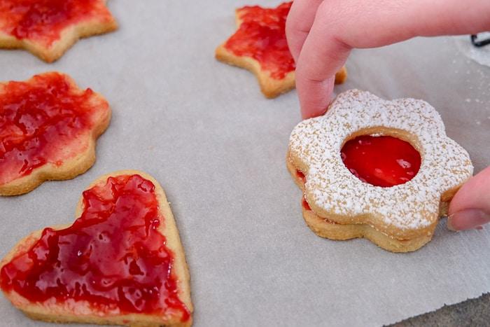 flower linzer jam cookie held in hand with other jam cookies beside