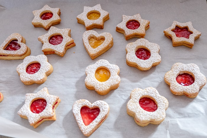 colorful linzer cookies on while parchment paper