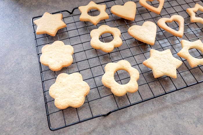 baked linzer cookies on black cooling rack on counter