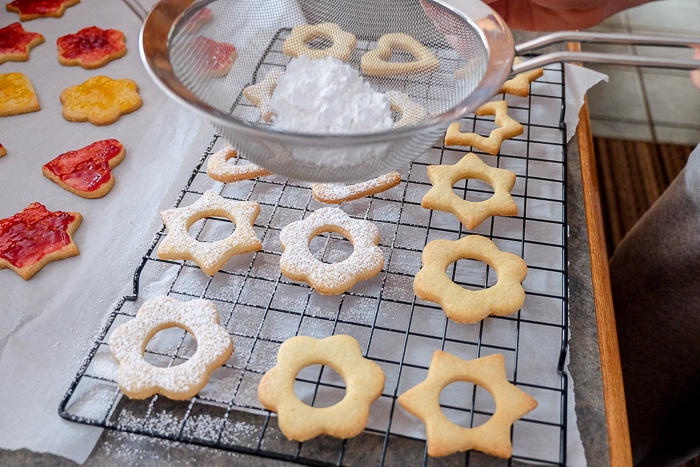 dusting powdered sugar through sifter onto baked linzer cookies on tray